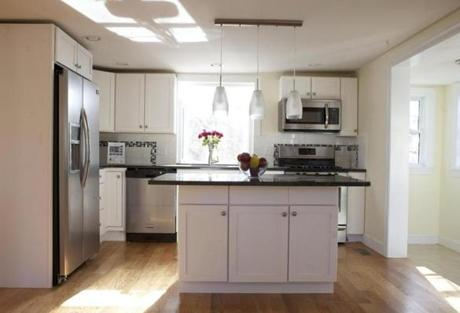 Built in 1940, this Cape now has a fully updated kitchen with new stainless steel appliances, a large island, with cabinets, and black granite countertop.